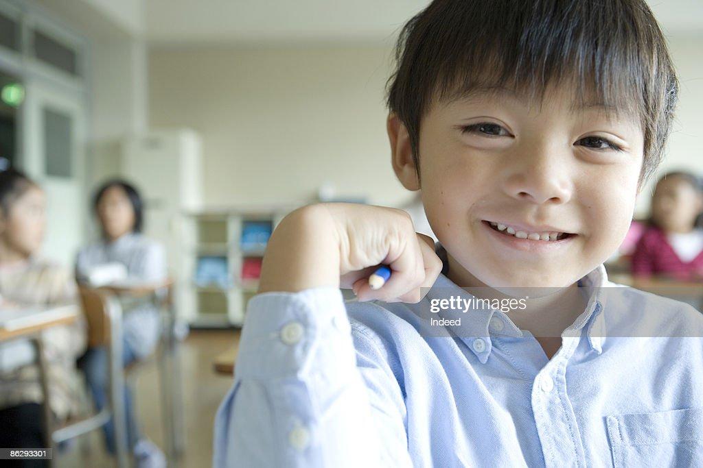 Schoolboy (6-7) smiling in classroom, portrait : ストックフォト