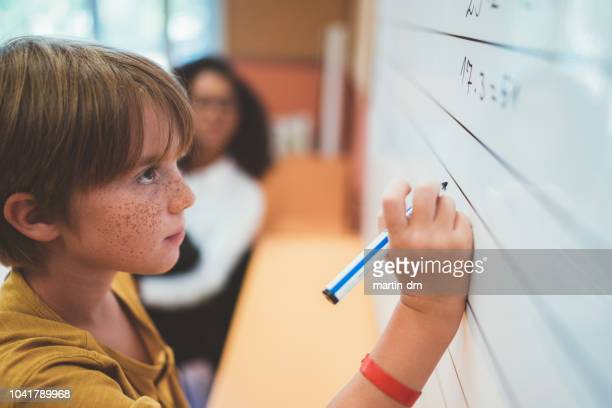 schoolboy solving math problem on whiteboard - mathematician stock pictures, royalty-free photos & images