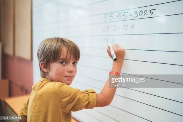 schooljongen oplossen van wiskunde op whiteboard - bulgarije stockfoto's en -beelden