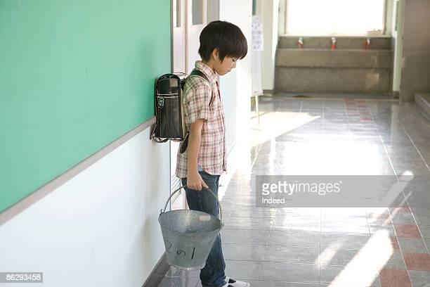 Schoolboy standing and holding bucket in corridor