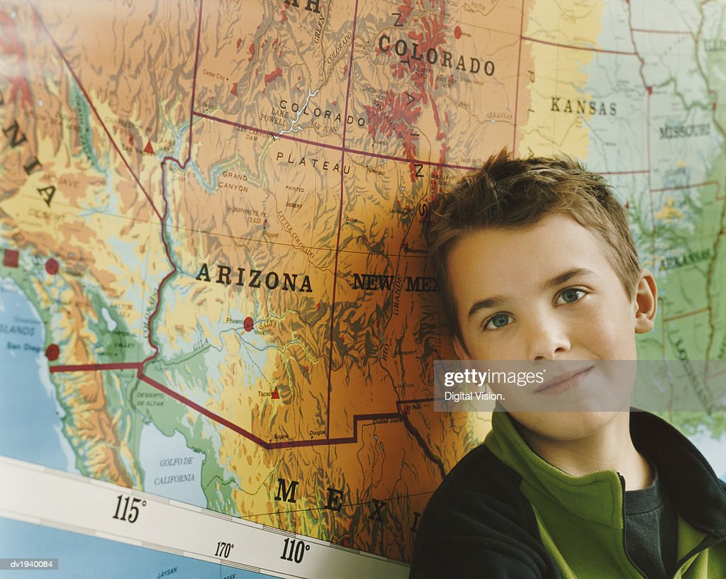 Schoolboy Standing by a Map of the USA in a Classroom : Stock Photo