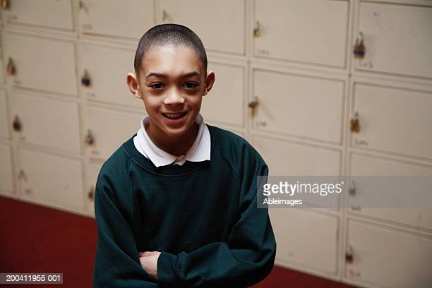 Schoolboy (8-10) standing by lockers, arms folded, smiling, portrait