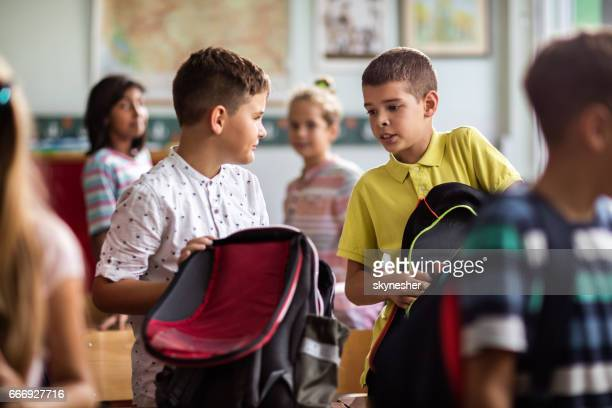 Schoolboy talking with classmate while packing his backpack.