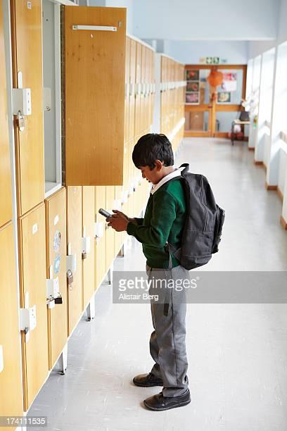 Schoolboy using cell phone in corridor