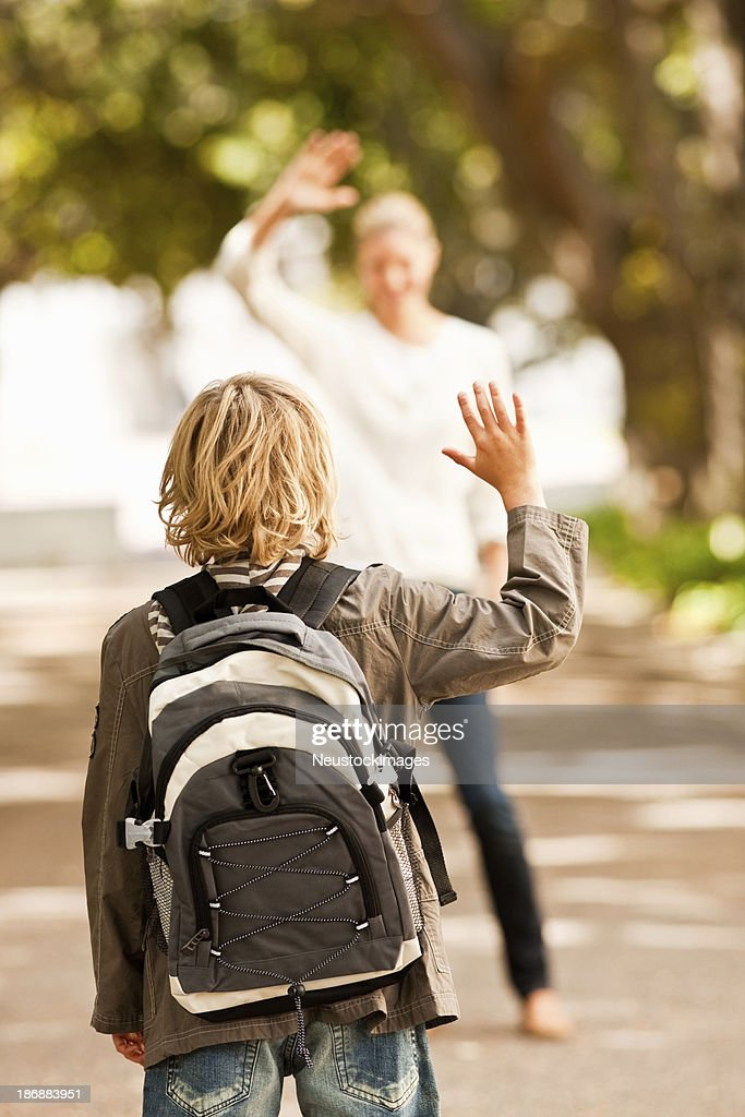 Schoolboy waving goodbye to his mother : Stock Photo