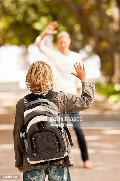 Schoolboy waving goodbye to his mother