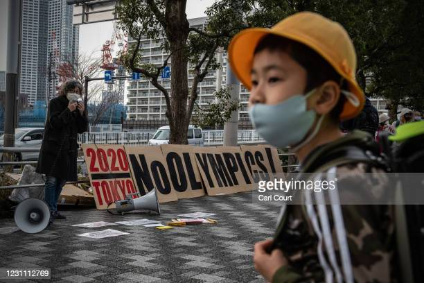 Schoolboy wearing a face mask walks past a banner saying No Olympics during a protest calling for the Tokyo Olympics to be cancelled on February 12,...
