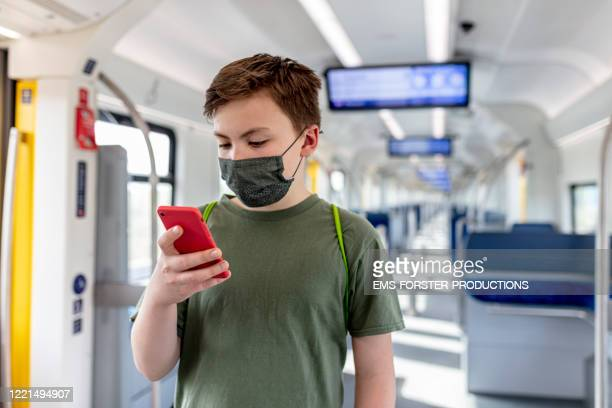 schoolboy wearing protective, self made cotton mask and gaming on phone while travelling in train s-ban - abstand halten infektionsvermeidung stock-fotos und bilder