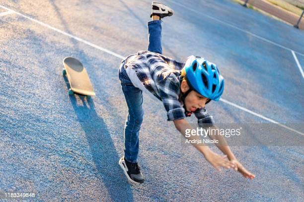 schuljunge mit einem helm fällt von seinem skateboard - schulkind nur jungen stock-fotos und bilder