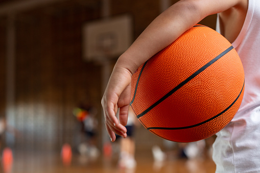 Schoolboy with basketball standing in basketball court 1133790384