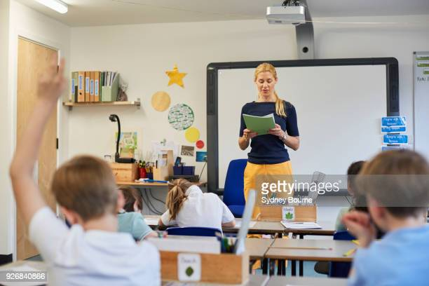schoolboy with hand raised in classroom lesson at primary school - classroom stock photos and pictures