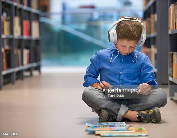schoolboy with headphones and tablet computer in library - science photo library stock pictures, royalty-free photos & images
