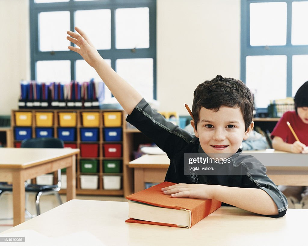 Schoolboy With His Hand Raised in a Classroom at Primary School : Stock Photo