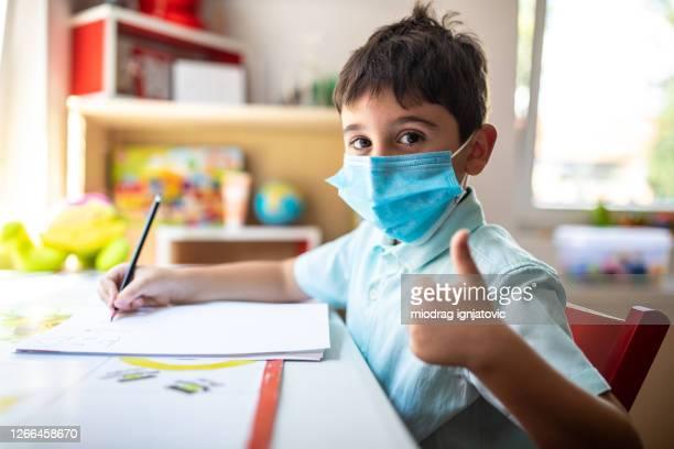schuljunge mit schützender gesichtsmaske am schreibtisch sitzend und daumen nach oben zeigen - unabhängige schulbildung stock-fotos und bilder