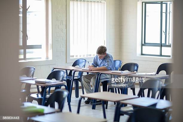 schoolboy writing in classroom - school detention stock pictures, royalty-free photos & images