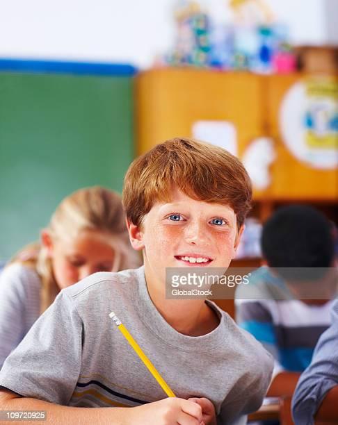 Scolaro scrivendo note in aula
