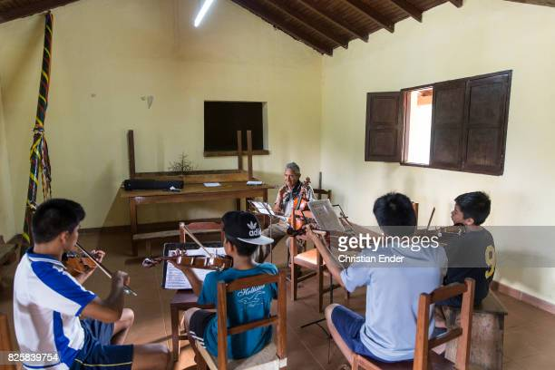 Santa Ana de Velasco Bolivia November 24 2016 Schoolboys are practicing to play Violin with their teacher inside a classroom next to the Jesuit...