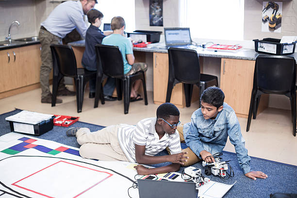 Schoolboys in robotics class testing vehicle on test track