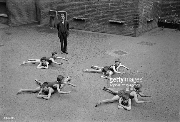 Schoolboys learning their swimming strokes in the playground.