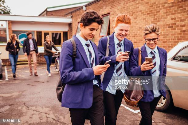 schoolboys on their mobile phones - school children stock photos and pictures
