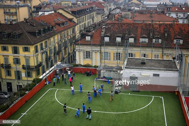 Schoolboys play football on a pitch situated on the roof top of the San Giuseppe College on January 31 2017 in Turin / AFP PHOTO / Marco BERTORELLO