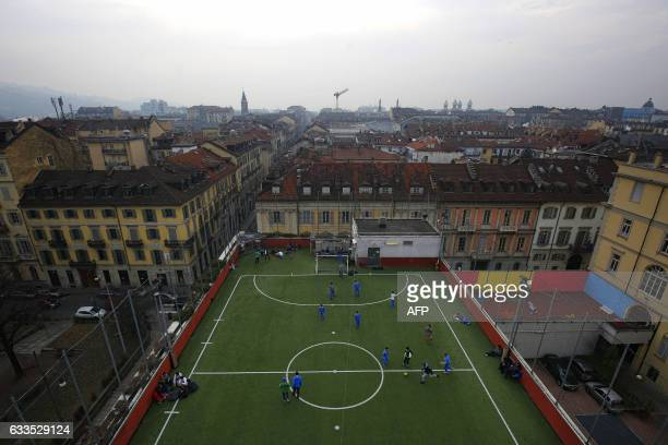 Schoolboys play football on a pitch situated on the roof top of the San Giuseppe College on January 31 2017 in Turin / AFP / Marco BERTORELLO