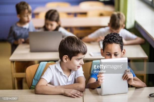 écoliers utilisant la tablette numérique sur une classe à l'école primaire. - groupe moyen de personnes photos et images de collection