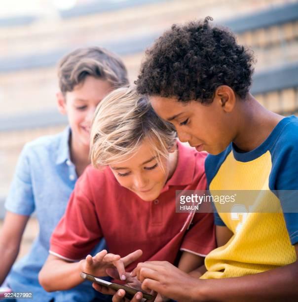 Schoolboys using smart phone outside school