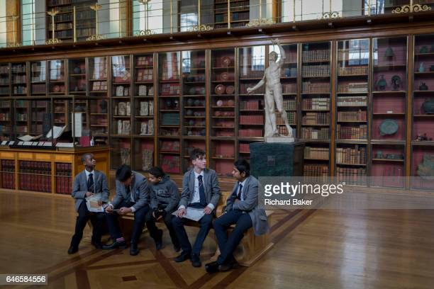 Schoolboys visiting the Enlightenment Gallery of the British Museum sit on a bench in front of Rondanini Faun a 2nd century Roman statue on 28th...