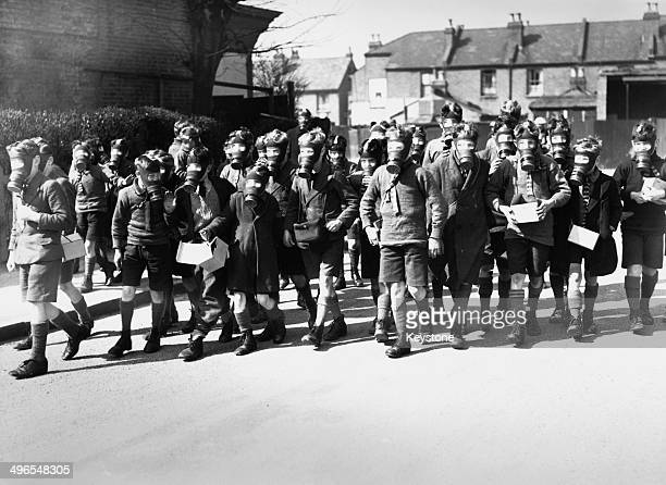 Schoolboys walking through a cloud of tear gas during a gas drill for civilians in Kingston upon Thames, 31st March 1941. The tear gas was used to to...