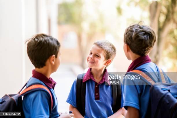 schüler mit rucksäcken sprechen in der schule - schuluniform stock-fotos und bilder