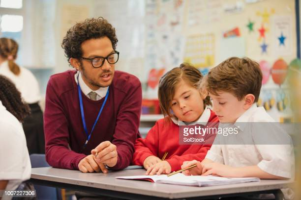 schoolboys work with their teacher in elementary class - teacher stock pictures, royalty-free photos & images