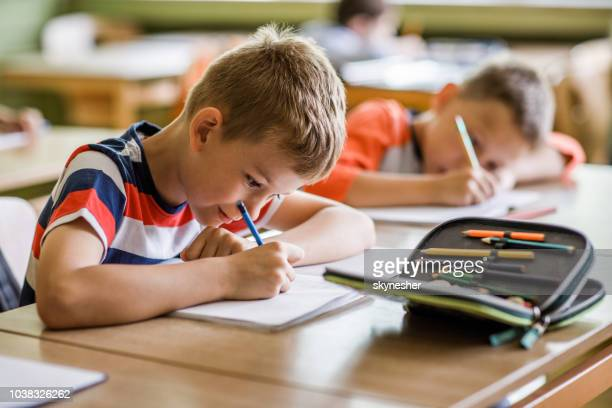 écoliers écrivant leur conférence dans les ordinateurs portables dans la salle de classe. - fournitures scolaires photos et images de collection