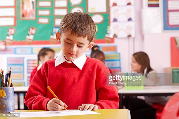 Schoolchild in a classroom writing on paper