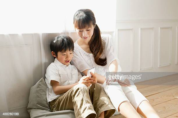 Schoolchild uses smartphone with mother