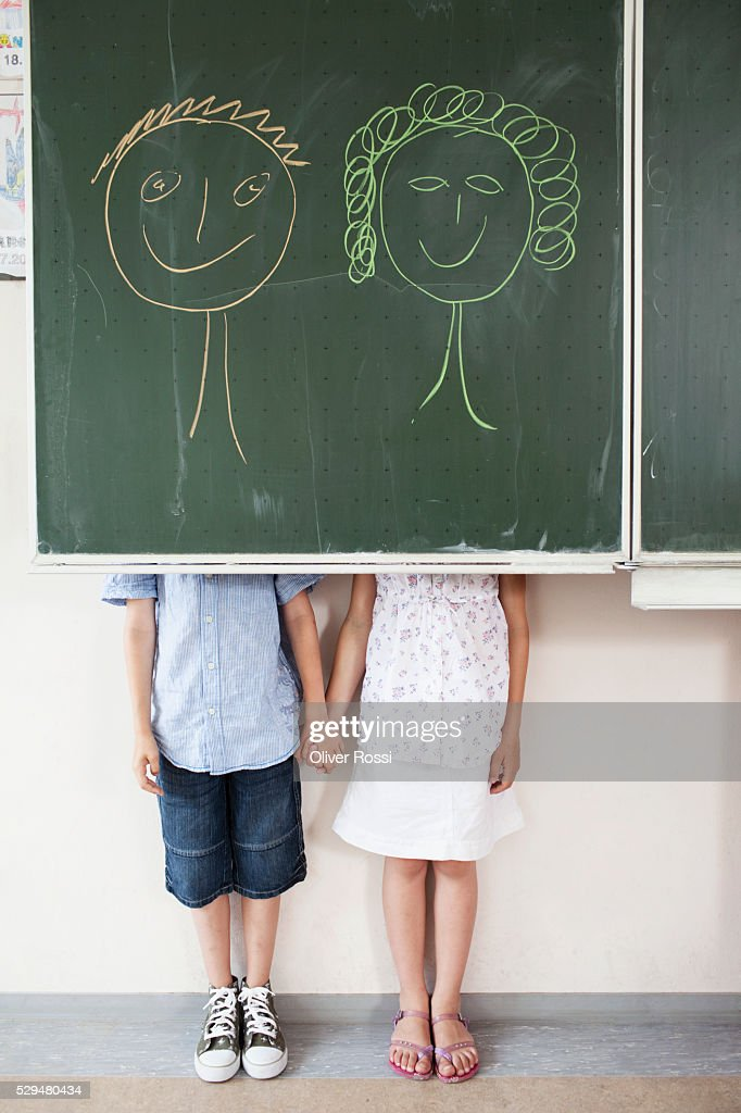 Schoolchildren and blackboard with smiley faces : Stock Photo