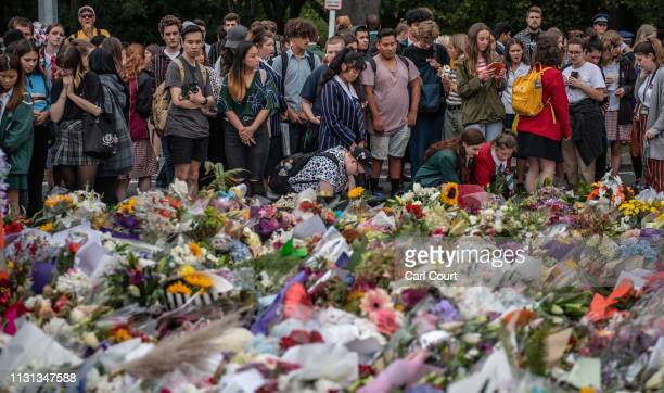 Schoolchildren and other wellwishers view flowers and tributes near Al Noor mosque on March 18 2019 in Christchurch New Zealand 50 people were killed...