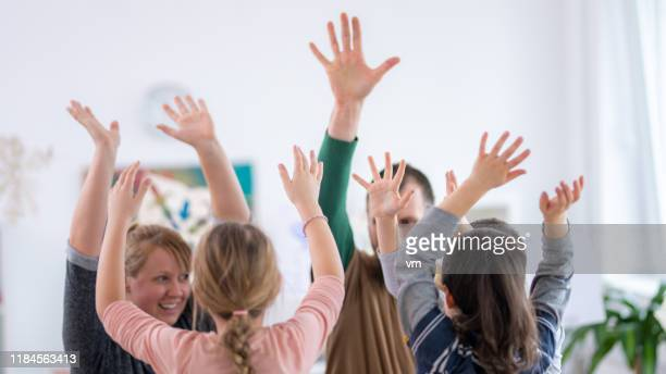 schoolchildren and teachers with arms raised - montessori education stock pictures, royalty-free photos & images