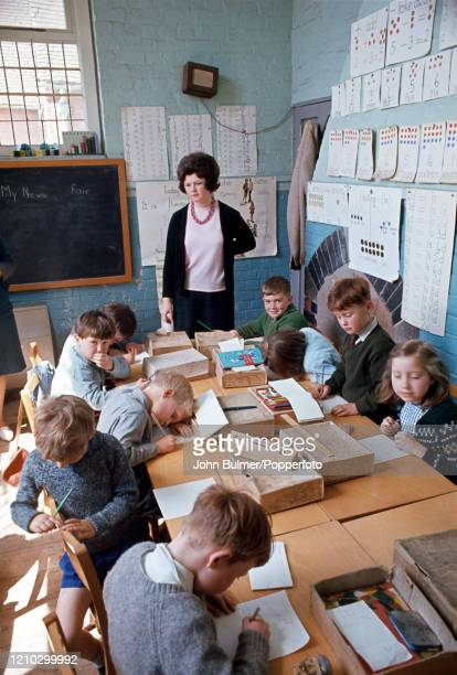 Schoolchildren and their teacher at work in a classroom of the village school in Pembridge England circa June 1966 During the summer of 1966 British...