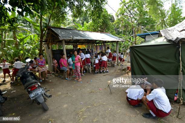 Schoolchildren buy and eat food next to a shop set up at a temporary evacuation centre at Ulakan village in the Manggis subdistrict in Karangasem...