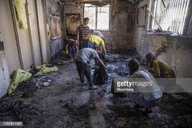 Schoolchildren clean out debris from a damaged Yeshiva classroom, following overnight protests in Lod, Israel, on Wednesday, May 12, 2021. Fierce...