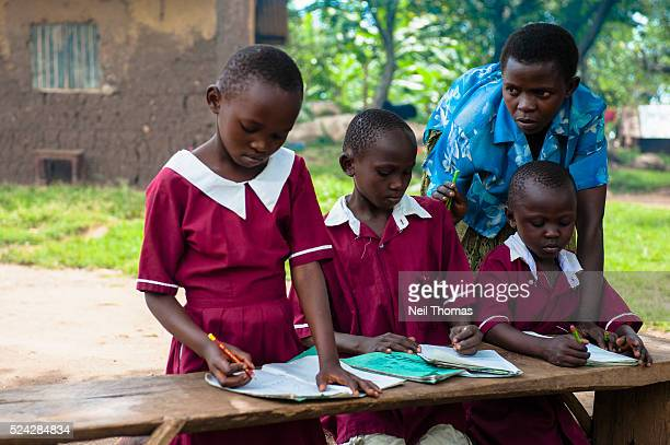 Schoolchildren complete their homework in the village of Bumweru Uganda Enrolment in primary education in developing regions reached 90 per cent in...