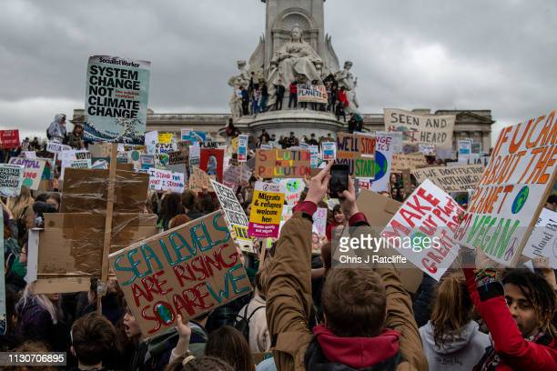 Schoolchildren gather around Queen Victoria Memorial at Buckingham Palace as they take part in a student climate protest on March 15 2019 in London...