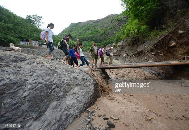 Schoolchildren get a helping hand as they cross a makeshift bridge to get to school after a mudslide that occurred in Ningnan southwest China's...