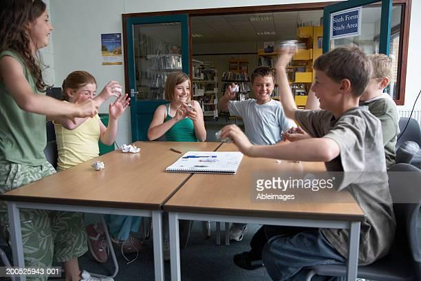 Schoolchildren (6-12) having paper fight in classroom, smiling