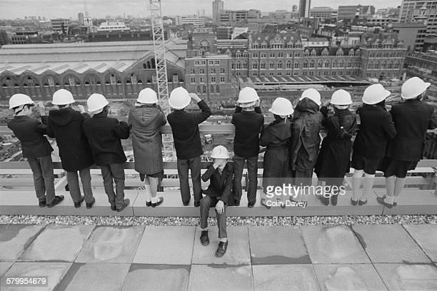 Schoolchildren in hard hats surveying the construction site around Liverpool Street Station in London 1986