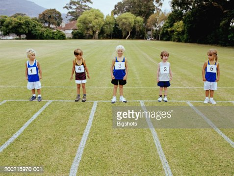 Schoolchildren (4-7) lined up at starting line of running track