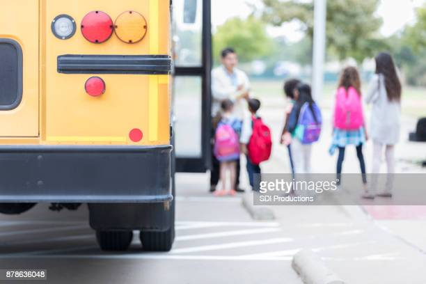 schoolchildren loading school bus - state school stock pictures, royalty-free photos & images