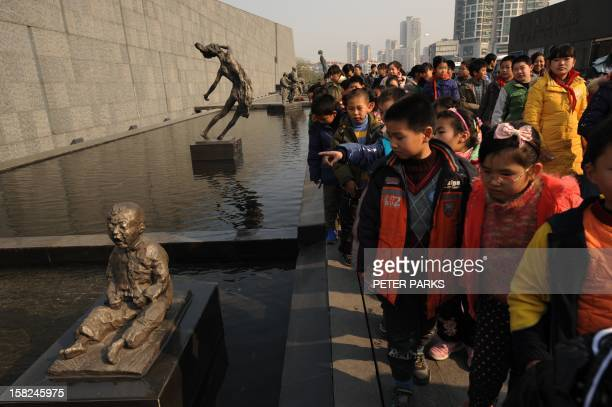Schoolchildren look at bronze sculptures depicting victims at the entrance to the Nanjing Massacre Memorial Museum on the eve of the Nanjing massacre...