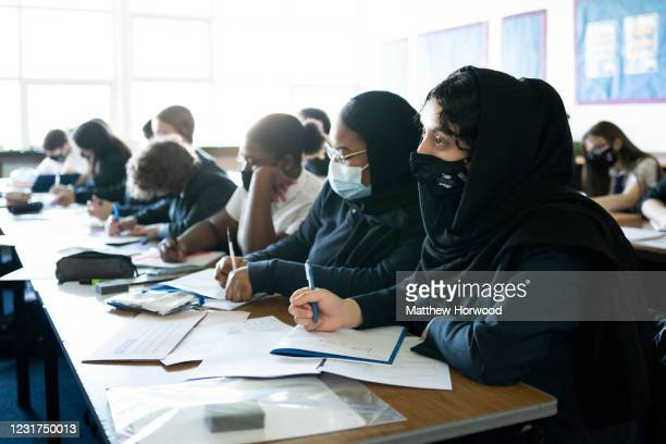Schoolchildren look on during a lesson at Willows High School on March 16, 2021 in Cardiff, Wales. Secondary schools in Wales reopen this week having...